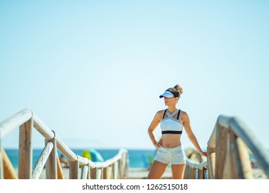young sports woman in fitness clothes on the seacoast relaxing after workout. 30 something years old woman entrepreneur learn healthy habits to live long interesting life.