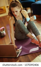 young sports woman in fitness clothes with dumbbell watching fitness tutorial on internet via laptop in the modern living room.