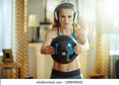 young sports woman in headphones in fitness clothes at modern home doing functional training exercises.