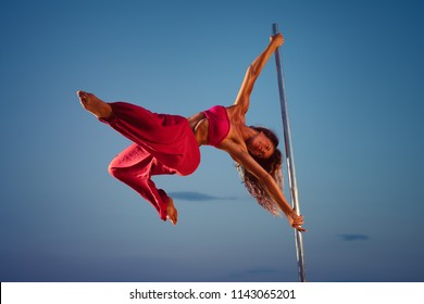 Young sports woman in pink clothing pole dancing at twilight on sunset blue sky background