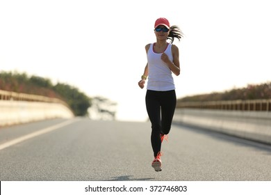young sports woman runner running on city road