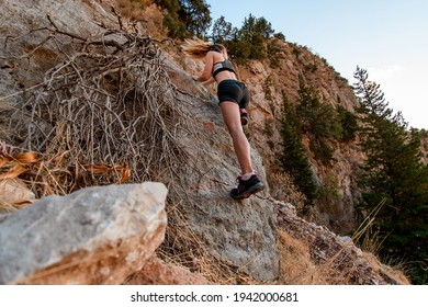 young sports woman skilfully climbs rocks of cliff near roots of tree. Hiking travel to Turkey