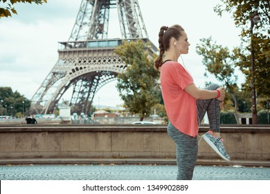 young sports woman in sport clothes stretching against Eiffel tower in Paris, France.