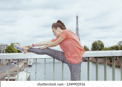 young sports woman in sport clothes stretching against clear view of the Eiffel Tower in Paris, France.