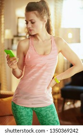 young sports woman in sport clothes with smartphone to track heart rate in fitness app at modern home.