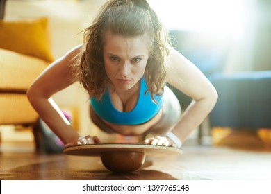 young sports woman in sport clothes in the modern house doing pushups using balance board.