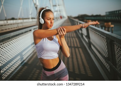 Young sports woman stretching arms before jogging