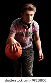 Young sportsman basketball player moving with ball. Over black background.
