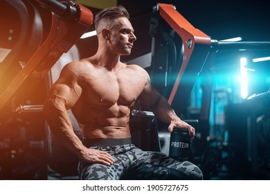 young sportsman bodybuilder with muscle body in gym