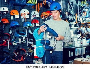 Young sportsman buys a sports equipment in the sports shop