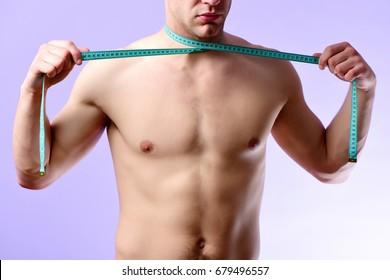 Young sportsman with cyan measuring tape on light purple background. Man with naked torso ties flexible ruler around his neck. Diet and healthy lifestyle concept. Sports regime idea.