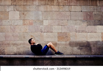 Young sportsman doing abdominal crunches against brick wall with copy space area for your text message or advertising content, sporty guy engaged an intensive fitness training in urban setting
