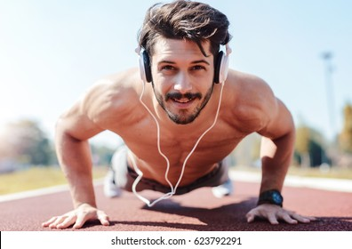 Young sportsman doing push ups and listening to music with headphones. Sport, fitness, street workout concept