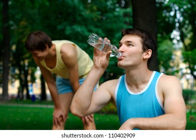 Young sportsman drinking water at the park with another person resting on the background