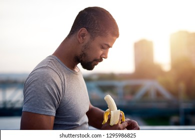 Young sportsman eating banana after training. Fitness and healthy eating.