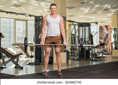 Young sportsman in gym. Strong guy standing with barbell in gym. Fitness stations on the background.