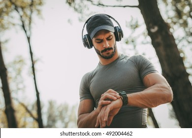 Young sportsman with headphones resting after training in the park and looking at stopwatch.