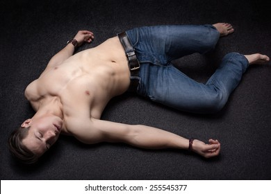 Young sportsman lying down unconsciously on apparent asphalt floor