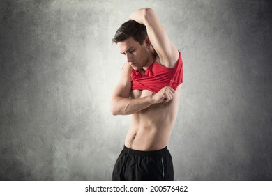 young sportsman putting take off on his red t - shirt