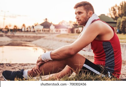 Young sportsman resting after a fitness training in the park. Sport, fitness, street workout concept