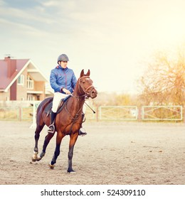 Young sportsman riding bay horse on equestrian competition.