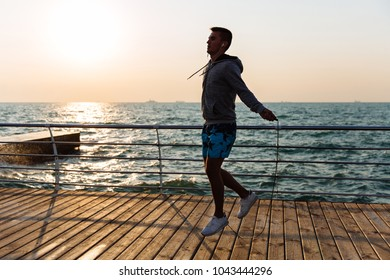 Young sportsman in sportswear, jumping with skipping rope, listening to music in earphones, on quay, near the sea. Workout.