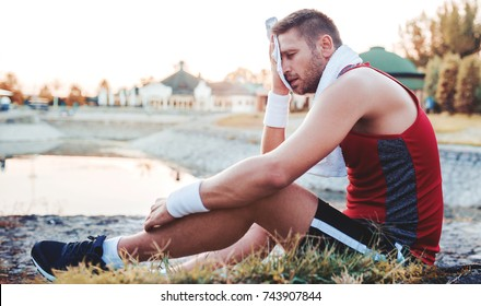 Young sportsman take a rest after fitness training in the park. Sport, fitness, street workout concept