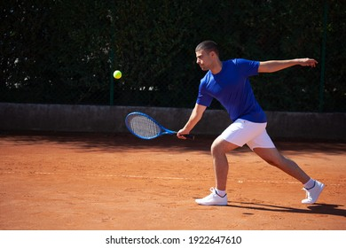 Young sportsman tennis player meets a shot of the opponent on a clay playfield