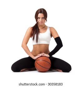 Young sportswoman with basketball sitting on white background.