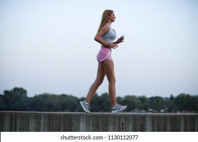 Young sportswoman brisk walking outdoors, urban style.