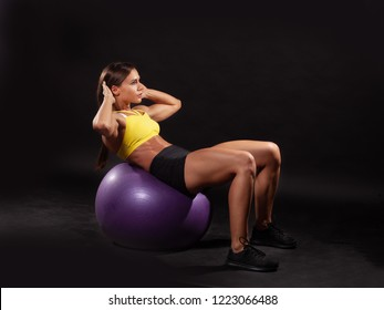 young sportswoman doing abs crunches with fitness ball isolated on black background