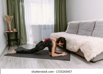 Young sportswoman doing exercises on a mat at home. Woman doing exercises aerobics warming up with gymnastics for flexibility leg stretching workout at home fitness
