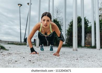 Young sportswoman doing pushups outdoors