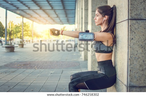 Young sportswoman doing squats against wall outdoors.