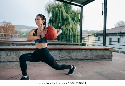 Young sportswoman doing stride exercises with a basketball outdoors