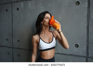 young sportswoman drink protein cocktail after workout in gym