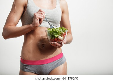Young sportswoman eating fresh healthy salad