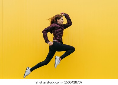 young sportswoman jumping with purple windbreaker, black leggins and white t-shirt