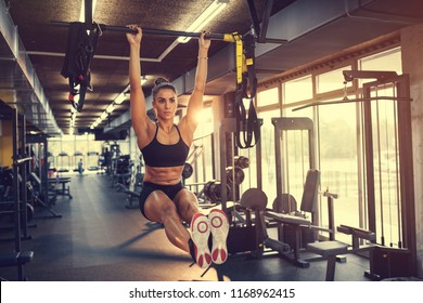 Young sportswoman lifting up on horizontal bar in gym