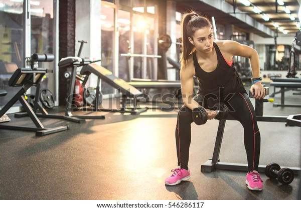 Young sportswoman lifting weights in gym.