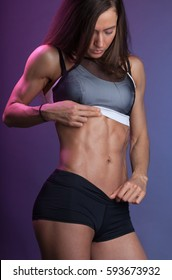 young sportswoman shows her relief abdominal muscles on purple background