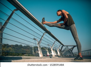 Young sportswoman standing on the bridge with one foot on the banister and leaning towards it