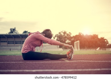 Young sportswoman stretching and preparing to run.woman worm up body with sunset background