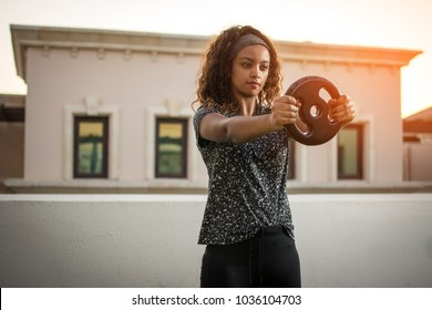 Young sportswoman workout with weight plate outdoors during sunset.