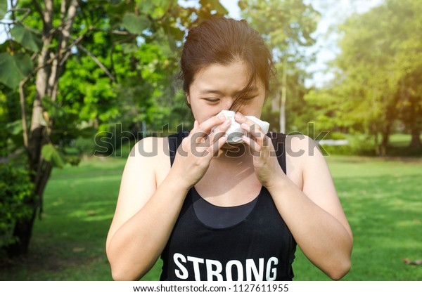 young sporty Asian woman feeling sick while exercise in the park