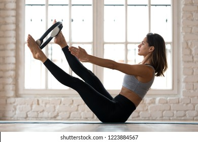Young sporty attractive woman doing toning pilates exercise for abs and inner thighs with exercise circle, open leg balance with pilates magic circle, indoor full length, at yoga studio or at home