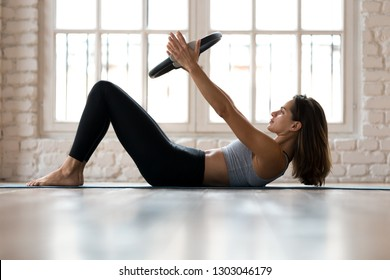 Young sporty attractive woman doing toning pilates exercise for abs with exercise circle, crunches for abdominal strengthening using pilates magic circle, wearing sportswear at yoga studio or at home