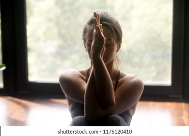 Young sporty attractive woman practicing yoga, doing Garudasana arms exercise, meditation pose, working out in yoga studio, close up view. Well being concept