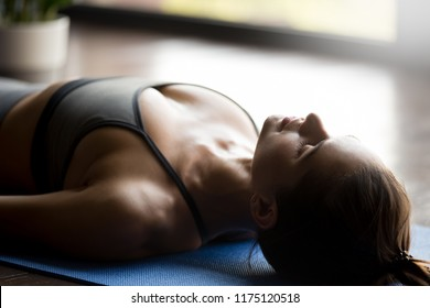 Young sporty attractive woman practicing yoga, doing Dead Body, Savasana exercise, Corpse pose, working out, wearing sportswear, grey top, indoor, face and body close up view, yoga studio