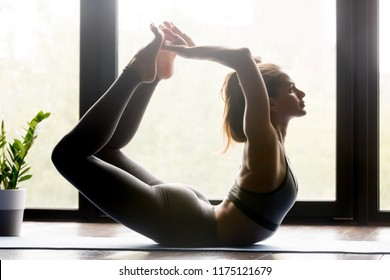 Young sporty attractive woman practicing yoga, doing Dhanurasana exercise, Bow pose, working out, wearing sportswear, grey pants and top, indoor full length, yoga studio. Side view